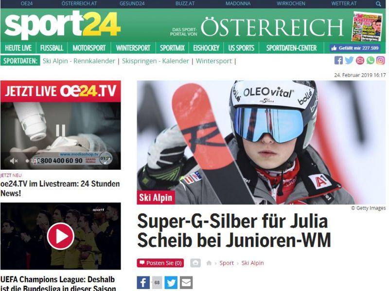 Das Bild zeigt Julia Scheib mit Helm und Skibrille mit ihrem Ski im Vordergrund.