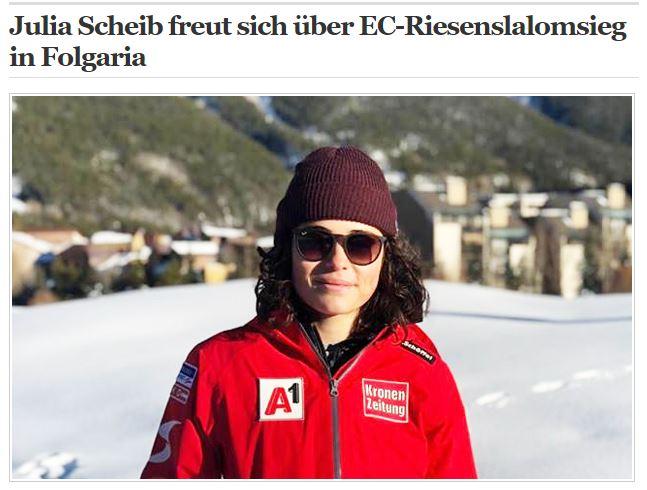 Das Bild zeigt ein Portrait von Julia Scheib in roter Jacke vor einer Stadt stehend.