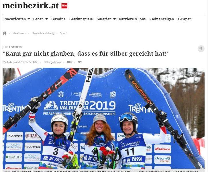 Das Bild zeigt Julia Scheib jubelnd links am Siegerpodest.